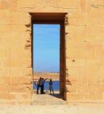 Turistas que disfrutan de una visita a Dakka, con la guía señalando en la arquitectura imagen de archivo