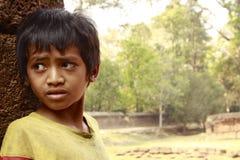 Turistas que esperan del niño camboyano para en Angkor Wat Foto de archivo libre de regalías