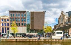 Turistas que esperan en línea para llegar adentro a la casa de Anne Frank en Amsterdam al lado del Westertoren fotografía de archivo