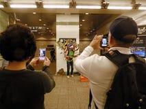 Turistas que fotografían al busker Foto de archivo