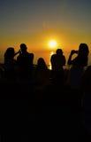 Turistas que fotografían puesta del sol Fotografía de archivo