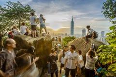 Turistas que fotografam Taipei 101 no por do sol Imagem de Stock Royalty Free