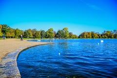 Turistas que gastam e que apreciam seus para relaxar o tempo na lagoa redonda no jardim de Kensington na frente do palácio de Ken fotos de stock