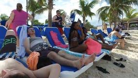 turistas que gozan y que mienten en los deckchairs en la playa, Bahamas metrajes