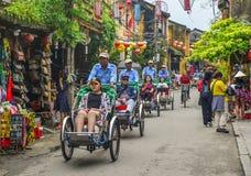 Turistas que llevan ciclos en la calle principal fotografía de archivo