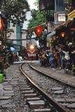Turistas que llevan la foto del tren en las vías que corren muy estrecho las casas en Hanoi foto de archivo