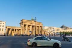 Turistas que miran la puerta de Brandeburgo en la ciudad de Berlín en Alemania mientras que un taxi conduce cerca fotos de archivo