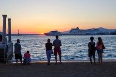 Turistas que miran la puesta del sol en Mykonos Foto de archivo