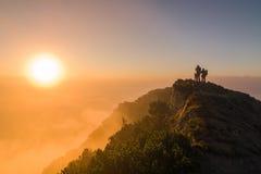 Turistas que miran la salida del sol en la cima de la montaña Fotografía de archivo libre de regalías