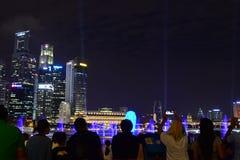 Turistas que miran las demostraciones de la luz en Singapur Foto de archivo libre de regalías
