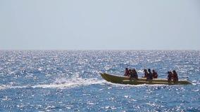 Turistas que montan actividades del deporte acuático del barco de plátano Cámara lenta almacen de video