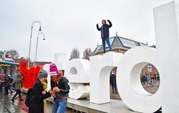 Turistas que presentan delante del lema Holanda de I Amsterdam imagen de archivo libre de regalías