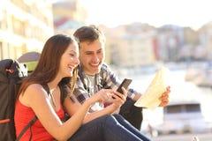 Turistas que procuram o lugar em um telefone esperto fotos de stock royalty free