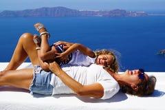 Turistas que relaxam no sol na ilha de Santorini fotografia de stock