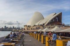 Turistas que se sientan en barra de la ópera delante de Sydney Opera House Fotos de archivo