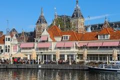 Turistas que se sientan en el restaurante al aire libre en Amsterdam imagenes de archivo