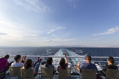 Turistas que se sientan en la cubierta de una nave que dirige al isla de Santorini Fotografía de archivo libre de regalías