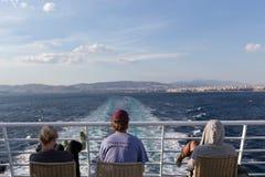 Turistas que se sientan en la cubierta de una nave que dirige al isla de Santorini Fotos de archivo