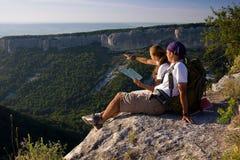 Turistas que sentam-se na montanha Fotografia de Stock Royalty Free