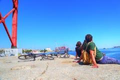 Turistas que sentam-se sob a ponte famosa de 25 de abril Fotografia de Stock Royalty Free