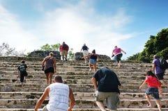 Turistas que suben las escaleras de ruinas mayas Foto de archivo
