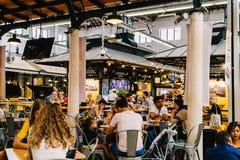 Turistas que têm o almoço no restaurante do mercado de Lisboa de Mercado de Campo de Ourique em Lisboa Fotos de Stock Royalty Free