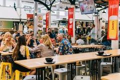 Turistas que têm o almoço no restaurante do mercado de Lisboa de Mercado de Campo de Ourique em Lisboa Fotografia de Stock Royalty Free
