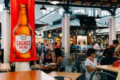 Turistas que têm o almoço no restaurante do mercado de Lisboa de Mercado de Campo de Ourique em Lisboa Fotografia de Stock