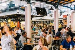 Turistas que têm o almoço no restaurante do mercado de Lisboa de Mercado de Campo de Ourique em Lisboa Imagens de Stock