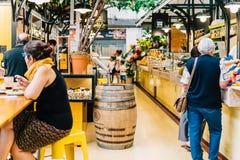 Turistas que têm o almoço no restaurante do mercado de Lisboa de Mercado de Campo de Ourique em Lisboa Foto de Stock