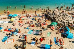 Turistas que têm o divertimento na água, relaxando e tomando sol na estância de verão do oceano de Cascais de Portugal fotos de stock royalty free