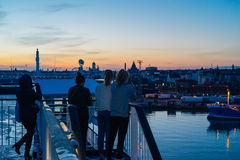 Turistas que tomam a foto e que apreciam a opinião do por do sol da cidade de Helsínquia Imagens de Stock