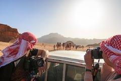 Turistas que toman la imagen de una conducción de automóviles a través del desierto de Wadi Rum, Jordania Foto de archivo libre de regalías