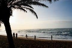 Turistas que toman las fotos en la puesta del sol en la playa de la puesta del sol Fotos de archivo