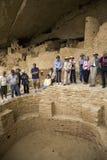 Turistas que vêem o kiva no penhasco do palácio do penhasco imagens de stock