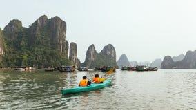 Turistas que vestem a veste de flutuação que kayaking na água esmeralda com as ilhas da pedra calcária no fundo no verão na baía  foto de stock