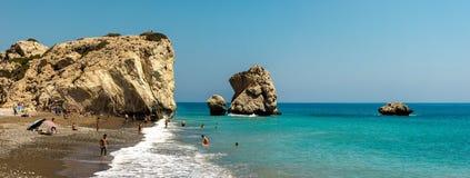Turistas que visitan a Aphrodite Rock y que nadan en una playa en Chipre Imagen de archivo