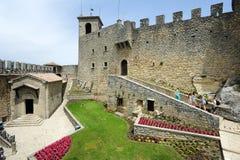 Turistas que visitan el La Rocca fortless en Borgo Maggiore, San Marin Imágenes de archivo libres de regalías