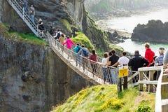 Turistas que visitan el puente de cuerda de Carrick-a-Rede en el condado Antrim de Irlanda del Norte imágenes de archivo libres de regalías