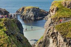 Turistas que visitan el puente de cuerda de Carrick-a-Rede en el condado Antrim de Irlanda del Norte fotos de archivo