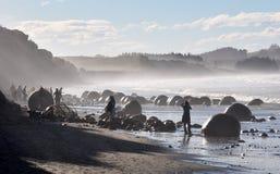 Turistas retroiluminados em pedregulhos de Moeraki, Nova Zelândia Imagem de Stock