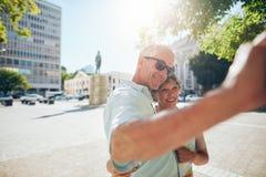 Turistas superiores afetuosos que tomam um selfie fora fotos de stock royalty free