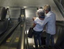 Turistas superiores dos pares na escada rolante que vai para baixo Fotografia de Stock