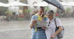 Turistas superiores no suporte chuvoso e em procurar do tempo a rota no mapa video estoque