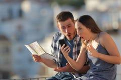 Turistas surpreendidos que encontram ofertas em linha em férias imagens de stock