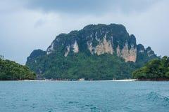 Turistas y barcos en la pequeña playa con el fondo de la montaña Foto de archivo