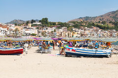 Turistas y barcos en la playa en la ciudad de Giardini-Naxos Imagenes de archivo