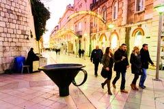 Turistas y ciudadanos que caminan a lo largo de una de las calles principales en la ciudad vieja de la fractura, Croacia Fotos de archivo libres de regalías