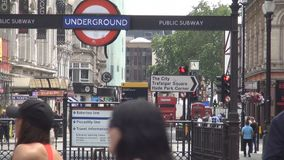 Turistas y entrada del subterráneo en el transporte público subterráneo de Londres