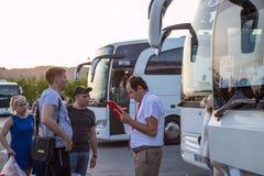Turistas y guía cerca del autobús que para cerca de aeropuerto en el punto de reunión de viajeros en Turquía fotos de archivo